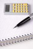 Business concept - note book with checked pages, pen and calcula Royalty Free Stock Images