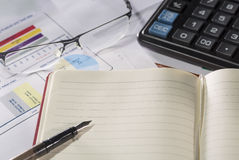 Business concept. Notebook with fountain pen, calculator, glasses on reports and paper with figures. Stock Images