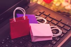 Business concept online shopping, paper shopping bags on notebook keyboard. Online shopping e-commerce or services on. The internet is a transaction of buying stock photos