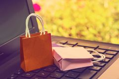 Business concept online shopping, paper shopping bags on noteboo. K keyboard. Online shopping e-commerce or services on the internet is a transaction of buying Stock Photography