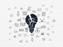Business concept: Light Bulb on wall background. Business concept: Painted black Light Bulb icon on White Brick wall background with  Hand Drawn Business Icons Stock Photo