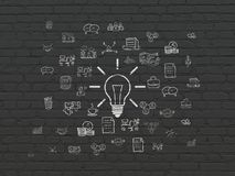 Business concept: Light Bulb on wall background. Business concept: Painted white Light Bulb icon on Black Brick wall background with  Hand Drawn Business Icons Royalty Free Stock Image