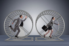 The business concept with pair running on hamster wheel Stock Images
