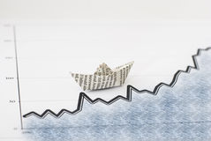 Business concept-paper boat on chart Stock Images