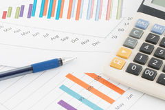 Business concept : Pen and calculator on graph background Royalty Free Stock Photo