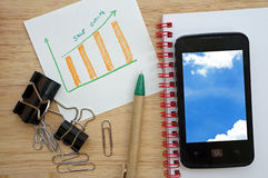 Business concept with pen, paperclip, mobile phone and financial table and graph Royalty Free Stock Photography