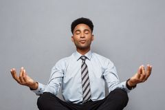 Business Concept - portrait of african american businessman doing meditation and yoga in before working. royalty free stock photography
