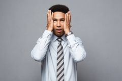 Business concept - portrait of frustrated stressed African American business man on grey background. Business concept - portrait of frustrated stressed African Royalty Free Stock Images
