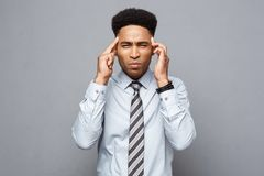 Business concept - portrait of frustrated stressed African American business man on grey background. Business concept - portrait of frustrated stressed African Stock Image