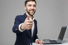 Business Concept - Portrait Handsome Business man showing thump up and smiling confident face in front of his laptop stock photos