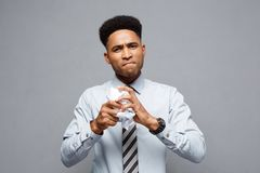 Business Concept - portrait of serious african american businessman holding crumpling report papers on hands. Stock Photo