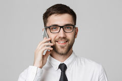 Business Concept - Portrait young handsome cheerful business man in suit talking on phone looking at camera. White background. Cop stock photo