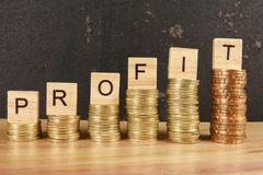 Business concept with PROFIT word on wooden plate onto hike trend stacked of coins. Business concept with PROFIT word on wooden plate onto hike trend stacked of royalty free stock image