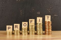 Business concept with PROFIT word on wooden plate onto hike trend stacked of coins.  royalty free stock photos