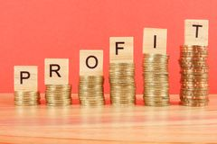 Business concept with PROFIT word on wooden plate onto hike trend stacked of coins.  stock image