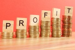 Business concept with PROFIT word on wooden plate onto hike trend stacked of coins.  royalty free stock image