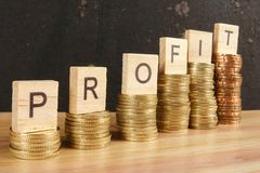 Business concept with PROFIT word on wooden plate onto hike trend stacked of coins. Business concept with PROFIT word on wooden plate onto hike trend stacked of stock photo