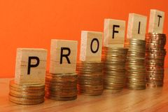 Business concept with PROFIT word on wooden plate onto hike trend stacked of coins.  stock photography