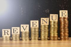 Business concept with REVENUE word on wooden plate onto hike trend of stacked of coins.  stock photo