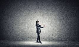 Business concept of risk with businessman wearing blindfold in empty concrete room Royalty Free Stock Photos