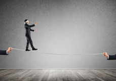 Business concept of risk support and assistance with man balancing on rope Stock Images