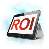 Business concept: ROI on tablet pc computer. Business concept: black tablet pc computer with text ROI on display. Modern portable touch pad on Blue Digital Royalty Free Stock Image
