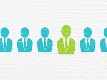 Business concept: business man icon on wall background. Business concept: row of Painted blue business man icons around green business man icon on White Brick Royalty Free Stock Photos
