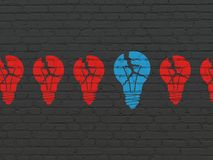 Business concept: light bulb icon on wall background. Business concept: row of Painted red light bulb icons around blue light bulb icon on Black Brick wall Stock Image