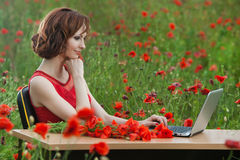 Business concept shot of a beautiful young woman sitting at a desk using a computer in a field. Royalty Free Stock Images