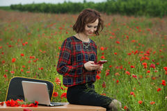 Business concept shot of a beautiful young woman sitting at a desk using a computer in a field. Stock Images