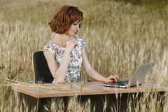 Business concept shot of a beautiful young woman sitting at a desk using a computer in a field. Royalty Free Stock Photo