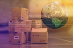 Business concept: Small cardboard boxes with a plane flies above. World map. Concept of  transportation, international freight, global shipping, goods or Stock Image