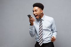 Business Concept - Stressful african american businessman shouting and screaming on mobile phone. Business Concept - Stressful african american businessman Royalty Free Stock Photography