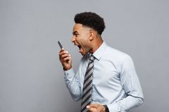 Business Concept - Stressful african american businessman shouting and screaming on mobile phone. Business Concept - Stressful african american businessman Royalty Free Stock Photos