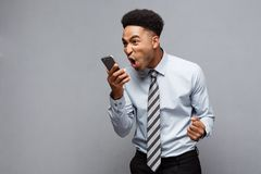 Business Concept - Stressful african american businessman shouting and screaming on mobile phone. Business Concept - Stressful african american businessman Stock Image