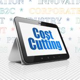 Business concept: Tablet Computer with Cost Cutting on display. Business concept: Tablet Computer with  blue text Cost Cutting on display,  Tag Cloud background Royalty Free Stock Images
