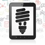 Business concept: Tablet Computer with Energy Saving Lamp on display. Business concept: Tablet Computer with  black Energy Saving Lamp icon on display,  Hand Royalty Free Stock Images