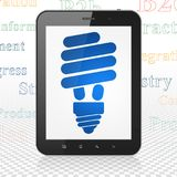 Business concept: Tablet Computer with Energy Saving Lamp on display. Business concept: Tablet Computer with  blue Energy Saving Lamp icon on display,  Tag Cloud Royalty Free Stock Photos