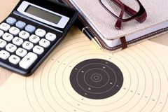 Target, calculator, pen, notebook, glasses - setting goals Royalty Free Stock Photo