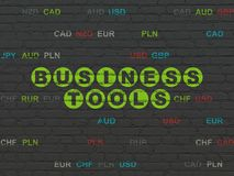 Business concept: Business Tools on wall background. Business concept: Painted green text Business Tools on Black Brick wall background with Currency Royalty Free Stock Photos