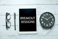 Business concept. Top view of glasses,pen,clock and tablet written with Breakout Sessions on white wooden background. Business concept. Top view of glasses,pen stock photos