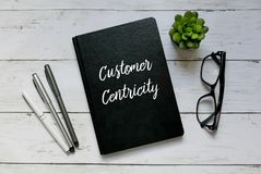 Business concept. Top view of glasses,plant,pen and notebook written with Customer Centricity. royalty free stock photo