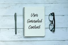 Business concept. Top view of pen,glasses and notebook written with User Generated Content. royalty free stock photo