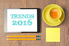 Business concept of trends for 2016 new year. Digital tablet with coffee cup on wooden desk. View from above. Business concept of trends for 2016 new year stock photos