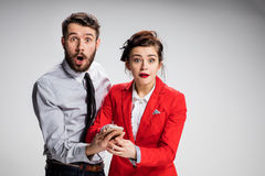Business concept. The two young colleagues holding mobile phone on gray background Stock Photo