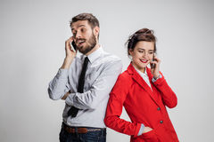 Business concept. The two young colleagues holding mobile phones on gray background Stock Images