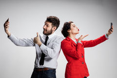Business concept. The two young colleagues holding mobile phones on gray background Stock Photos