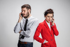 Business concept. The two young colleagues holding mobile phones on gray background Stock Photo