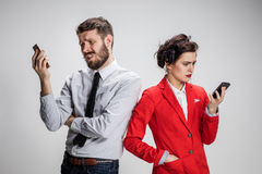 Business concept. The two young colleagues holding mobile phones on gray background Royalty Free Stock Photo