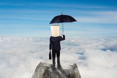 Business concept: Unknown businessman carrying umbrella on top of mountain.  Royalty Free Stock Image